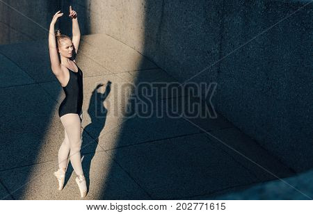 Ballet dancer practicing dance moves outdoors. Dancer standing tall on her toes in pointe shoes practicing her dance steps.
