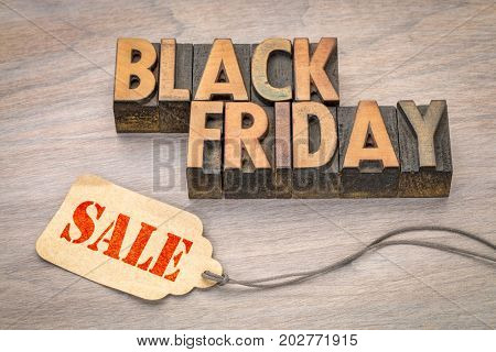 Black Friday sale banner  in vintage letterpress wood type blocks with a price tag against grained wood