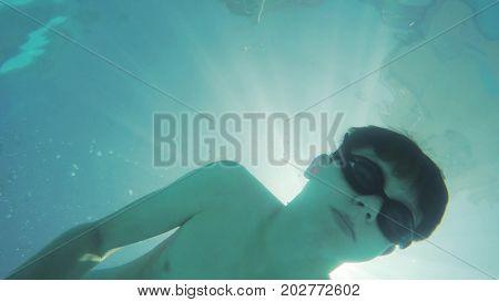Boy teenager swims under the water in pool. Happy childhood underwater rest bathe boy