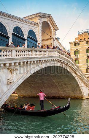 Venice, Italy - May 17, 2017: Rialto Bridge with gondola on the Grand Canal. Rialto Bridge (Ponte di Rialto) is one of the main tourist attractions of Venice.