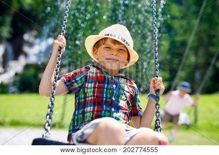 Funny kid boy having fun with chain swing on outdoor playground during rain. child swinging on warm rainy summer day. Active leisure with kids. Happy crying boy with rain drops on face