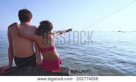 Boy and girl on sea. A boy and girl are sitting on the rocks on the sea view from the back of a romance happy childhood and dreams