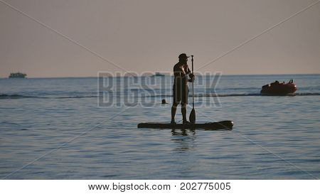man is floating while standing in ocean paddle board. by sea on a boat. Holiday on the Black Sea
