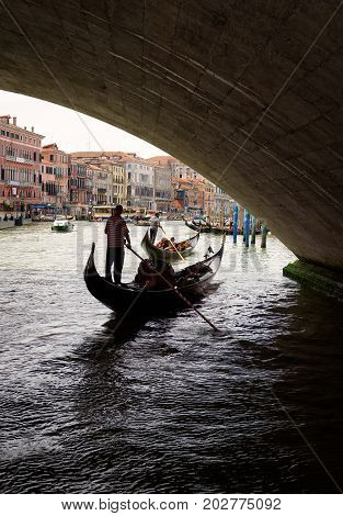 Venice, Italy - May 19, 2017: Gondolas with tourists are sailing under the Rialto Bridge on the Grand Canal. The gondola is a traditional romantic transport in Venice.