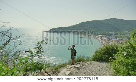 Boy teenager tourist travels through mountains by the sea. Boy traveler drinks water thirsty