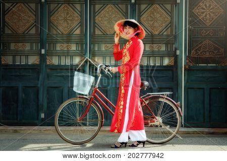 Vietnam woman wearing red Ao Dai traditional dress and a bike ride in Mu Cang Chai Yen Bai. poster