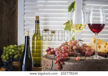 Still life of couple of glasses white and red wine with wooden keg. Wine bottles glasses of white and red wine with cheese and grape on a old wooden barrel. Wine tasting and production concept.