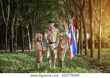 Scout and Boy Scout leader teacher holding Thai flag