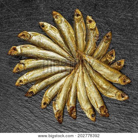 arrangement with lots of fresh smoked sprats on dark stone slab