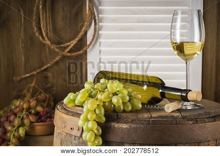 Still life of white wine with wooden keg with copy space. Wine bottle glass of white wine and bunch of grapes on a old wooden barrel. Wine tasting and production concept.