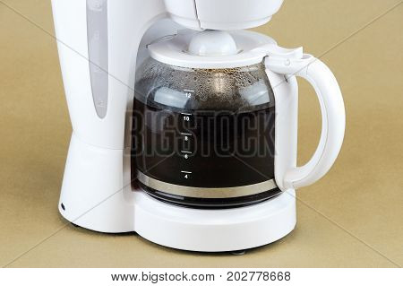 close up on coffee maker isolated on brown background