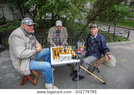 St. PETERSBURG, RUSSIA - SEP 2, 2017: Pensioners play chess in the courtyard of an apartment building. In Petersburg among the population the share of pensioners is approximately 24.4 percent.