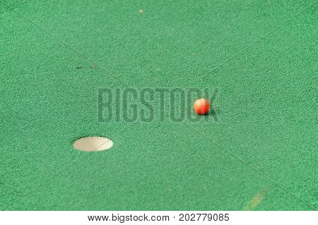 golf ball on plastic turf carpet near the hole