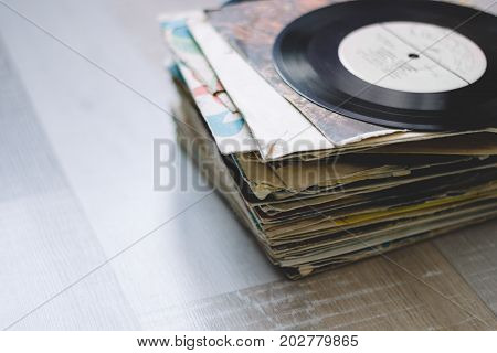A Stack Of Old Vinyl Records On A Wooden Floor