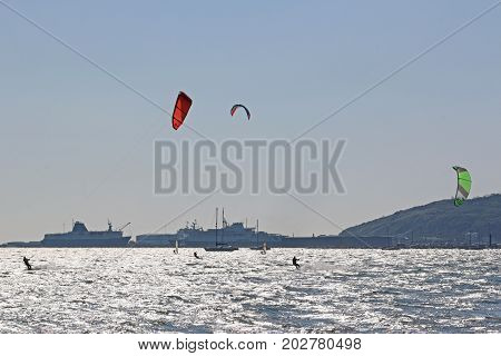 Paragliders riding their boards in Portland Harbor, Dorset