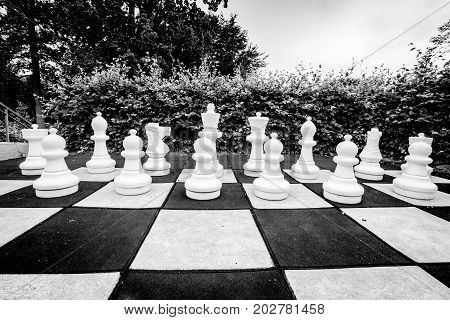 Black and white photo of a game of chess in an outdoor environment