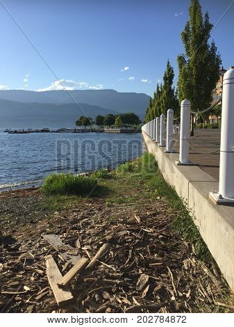 Beach with debris driftwood and grass. Lake shoreline with cement wall and white railings. Dock with small airplane and mountains background of lake in summertime.