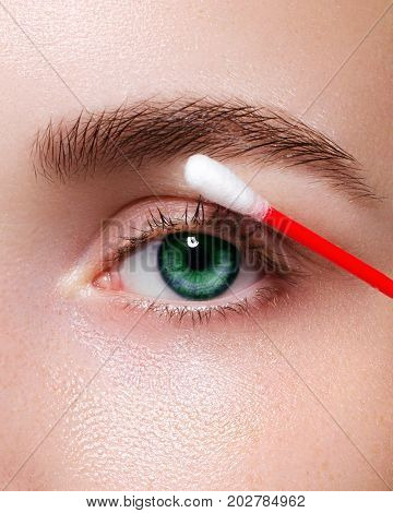 The woman care of skin around eyes a Q-tip. Macro shot of beautiful green eyes with pure fresh leather. Natural cosmetics. Cosmetology medicine Spa