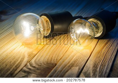 Two burning incandescent bulbs on a wooden table. Background with an empty space for your text