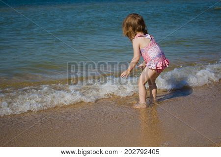 a small child walks cautiously into the sea. hot sunny day
