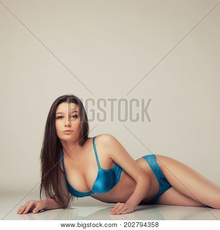 beautiful attractive girl in blue lingerie lying on floor
