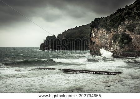 Dramatic landscape with cliffs on sea shore during storm with big stormy waves and dramatic sky with rain in fall season on Balkan sea coast