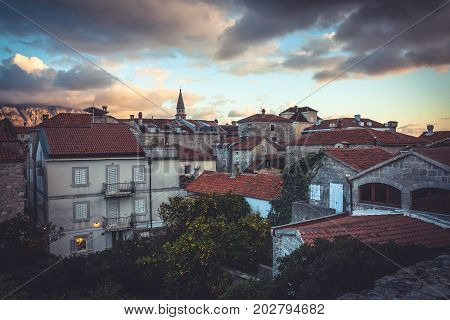 Old European city skyline with orange tile roofs and dramatic sky in antique architecture with trees in old European town Budva in Montenegro during sunset
