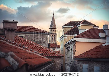 European city skyline with orange tile roofs and tower in front of dramatic sunset sky with antique architecture in old European town Budva in Montenegro