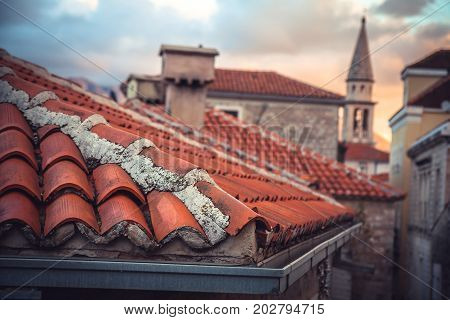 European city skyline with old tile roof in front of dramatic sunset sky with antique architecture and blurred background in old European town Budva in Montenegro