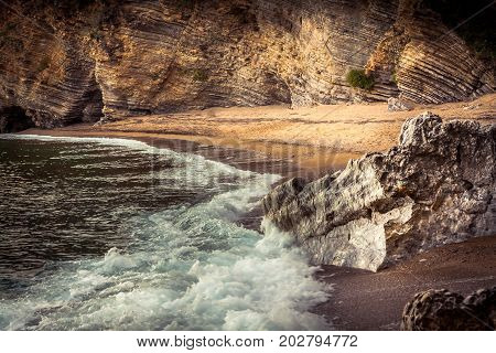 Overcast rocky beach landscape with cliffs and stones on Balkan coastline in beige and orange colors poster