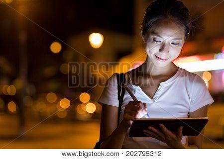 Designer using digital tablet in the city at night