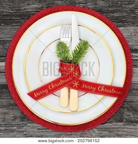 Christmas dinner table place setting with plates, merry christmas ribbon with napkin, cutlery and fir on red mat on rustic wood background.