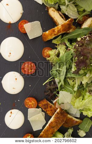 caesar salad with cheese and tomatoes on black ceramic plate