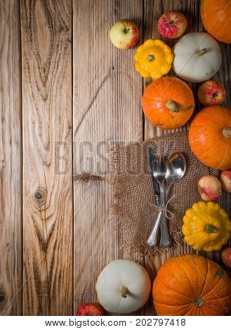 Tableware pampkins and apple on the wood background
