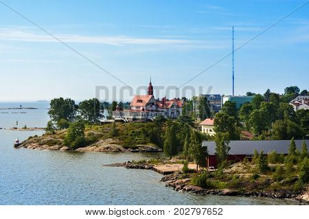 A house with a red roof and domes standing on the high rocky promontory of the Baltic gulf near the port of Helsinki Finland.