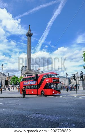 London UK - July 21 2017: Looking at Nelson's Column Trafalgar Square from The Strand. Shows a red London bus at the traffic lights and the street in the foreground.
