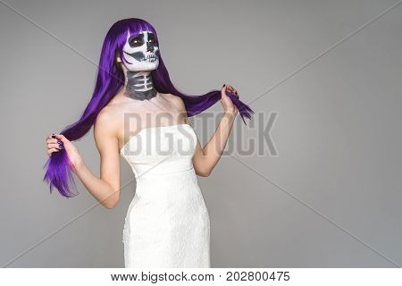 Portrait of woman with terrifying halloween skeleton makeup and purple wig and wedding dress over gray background