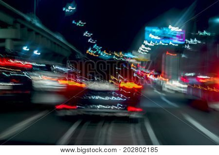 Fast driving traffic at night, blue colors. Abstract blurred background of urban moving car with blur bright brake lights at night. Auto, city street lights and speed. Selective focus