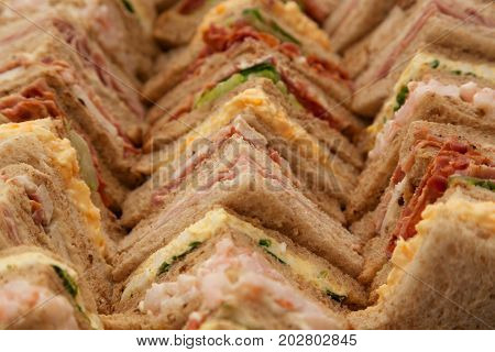 Platter of a selection of sandwiches cut into triangles and lined up on a tray.
