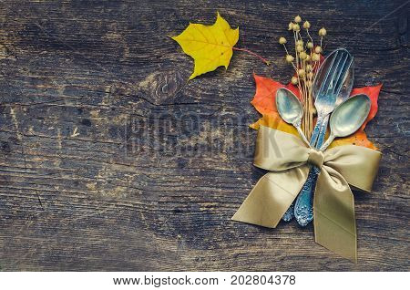 Thanksgiving autumn place setting with cutlery and arrangement of fall leaves and ribbon on wooden background with place for text. Thanksgiving holidays background concept. Copy space. Top view.