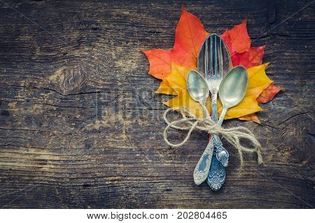 Thanksgiving autumn place setting with cutlery and arrangement of fall leaves and rope on wooden background with place for text. Thanksgiving holidays background concept. Copy space. Top view.