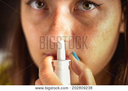 The Girl Uses A Spray For Her Nose. Treatment Of Colds, Flu.