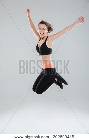 Full length image of happy jumping fitness woman over gray background