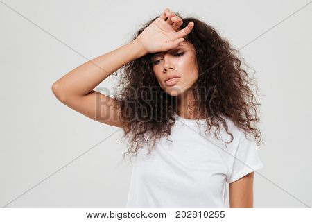 Tired curly woman with closed eyes holding hand on forehead over gray background