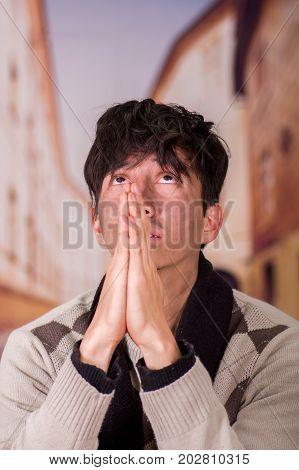 Portrait of a homeless young man in the streets, praying to god for food in a blurred background.