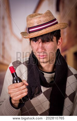 Close up of a sad homeless young man in the streets, wearing a hat and a scarf, and holding a bottle of wine in his hand, in a blurred background.