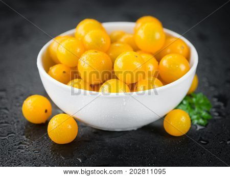 Some Yellow Tomatoes On A Dark Slate Slab
