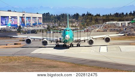 Boeing 4-engine double deck 747 jet airplane being tested on the runway at the Boeing factory located in Everett Washington USA. The planes in production are wrapped in green coating. The picture was taken in Everett Washington USA on July 31 2017.