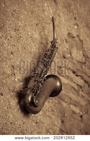 An old and dusty brass saxophone displayed on a rendered wall that is need of repair