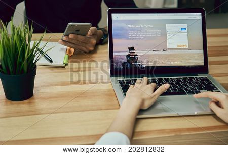 Bangkok Thailand - September 5,2017 : Women using Laptop open Twitter application showing on screen is an online social networking and service that enables users to send and read message